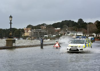 Police car driving through floods at Shore Road, Poole. Poole Harbour flooding. Sandbanks floods.