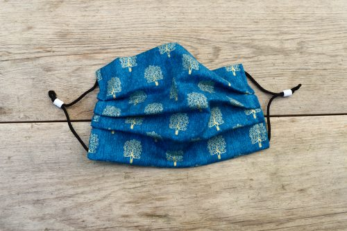 Blue face mask with gold trees, 100% cotton.