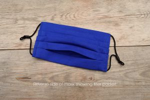 Reverse side of pleated royal blue face mask, 100% cotton, with nose wire and space for filter.