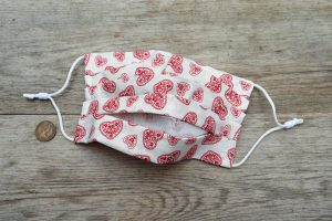 Reverse side of pretty cotton face mask with hearts, nose wire and filter pocket.