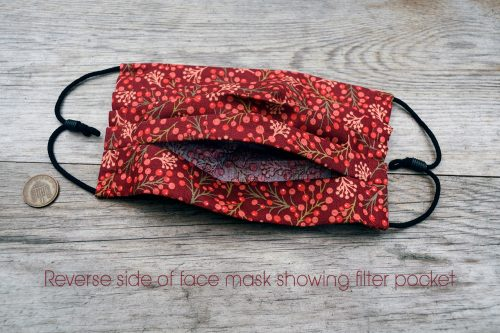 Reverse side of red berries face mask. Washable, 100% cotton, nose wire, filter pocket. Adjustable ear loops